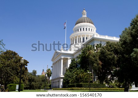 California state capitol and grounds with flags against a blue sky. - stock photo