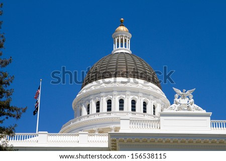California statehouse dome showing architectural details against a blue sky background.