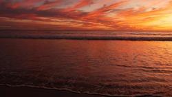 California summertime beach aesthetic, golden sunset. Vivid dramatic clouds over pacific ocean waves. Santa Monica popular resort, Los Angeles CA USA. Atmospheric moody purple evening sundown in LA.