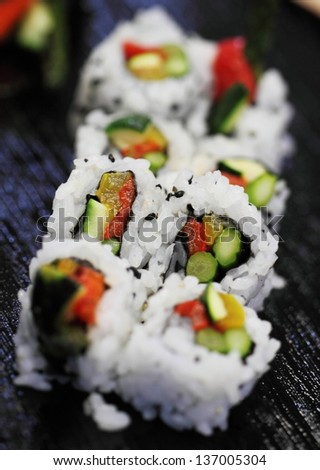 California sushi roll platted on a black plate.