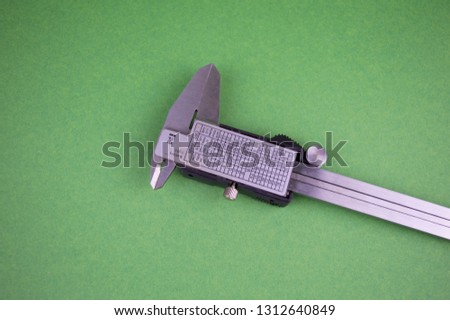 caliper with digital screen on a green background, there is free space to fill the text