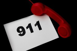 Call 911 and emergency call concept, text 911 on paper and phone isolated on black.