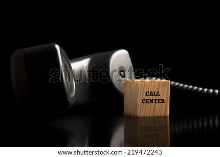Call Center and communications concept with a landline telephone handset lying off the hook on a dark reflective surface alongside a wooden block with the text - Call Center.