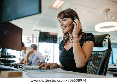 Call center business woman talking on headset. Caucasian female in customer service position talking on the phone. #706538974