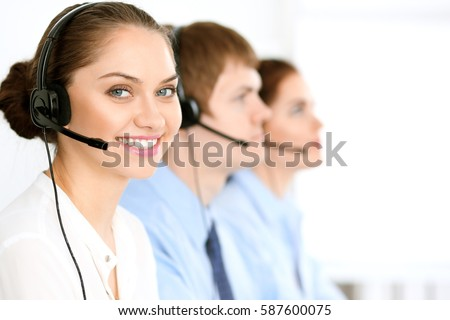 Call center operators. Focus at brunette business woman in headset #587600075