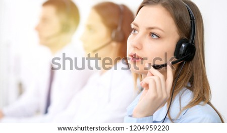 Call center operators. Focus on young cheerful smiling woman in headset. Business and customer service concepts