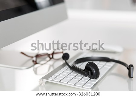 Call center service operator empty working place. Headset, glasses, keyboard and monitor at helpdesk employee workplace. Effective and efficient business information, help and support concept