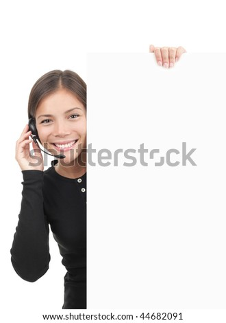 Call center woman with headset holding blank white billboard sign. Smiling and friendly young mixed race chinese / caucasian secretary or telemarketing assistant isolated on white background.