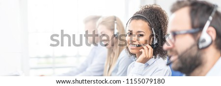 Call center worker accompanied by her team. Smiling customer support operator at work. Young employee working with a headset. #1155079180