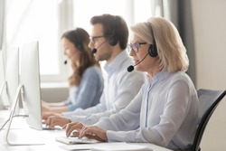 Call center workers working use headset look at computer screen, focus on blond aged female employee receive record and relay messages from customers, provide assistance and support distantly concept