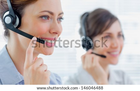 Call centre agents with headsets at work smiling