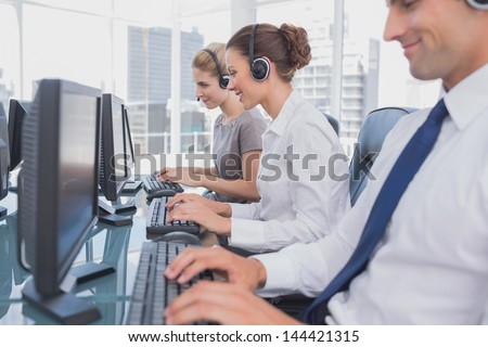 Call centre employees at work on computer in office