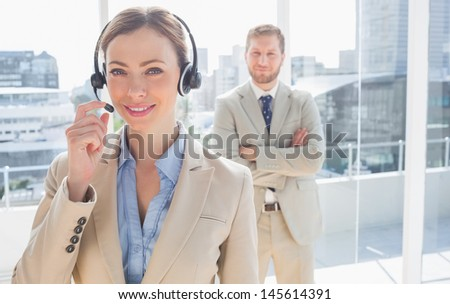 Call centre worker standing with colleague behind her in a bright office