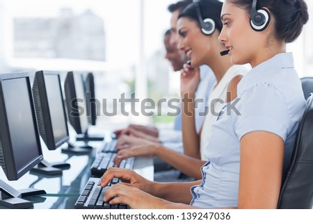 Call centre workers sitting in line while helping people on computers