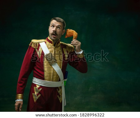 Call chicken. Young man in suit as Nicholas II isolated on dark green background. Retro style, comparison of eras concept. Beautiful male model like historical character, monarch, old-fashioned. Photo stock ©