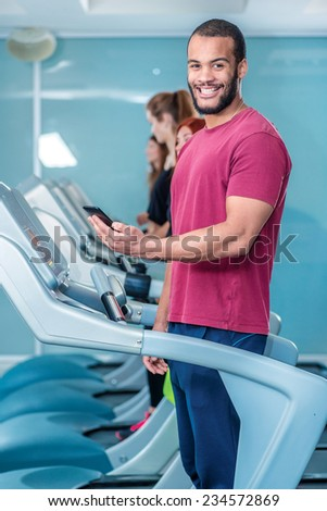 Call customer during sports activities. Sport runs on a treadmill and looking at the camera. Athlete dressed in sports uniforms and running in the gym.