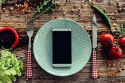 Call for delivery. Top view of plate and smart phone laying on the rustic wooden desk with vegetables around