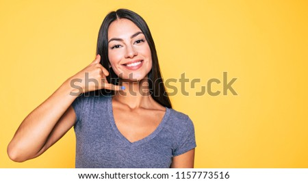 Call me. Communication, sign and symbols. Close up Portrait of cute attractive brunette woman posing on yellow background in casual wear