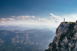 call of nature on the Otscher mountain. The girl in black sportswear stretches on a rock massif. Dangerous place. View of the Austrian Alps. Mountain girl on the edge of a rock.