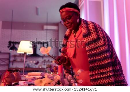 Calla. African american plump fortune-teller wearing eyewear taking a flower