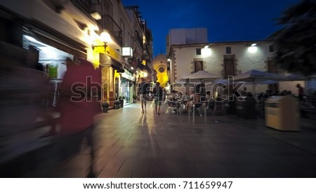 Callela night city life, small Spain Catalonia Costa Brava town pedestrian street with restaurants, souvenir shops, bars, cafe, tourists walking along long road at late evening - Shutterstock ID 711659947