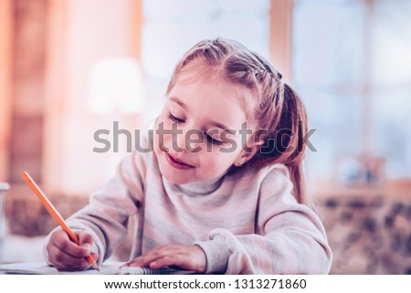 Calligraphic handwriting. Young lady in charming pink sweatshirt writing calligraphic handwriting tasks for school #1313271860