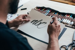 Calligraphy artist or student practices spelling words and letter with black ink brush on white canvas, sits behind table with different kinds of tools, pens, brushes and watercolors set up