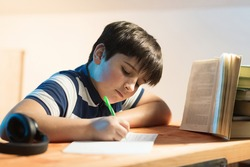 Calligraphy classes. boy in front of a book while busy rewriting text