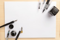 Calligraphy concept, accessories and tools for handwriting,ink, brush,writing training,blank sheets of white paper and cardboard crafting on wooden table,Top view, place for text