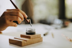 Calligraphy concept. Close-up image of artist holding fountain pen.