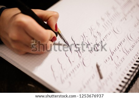 Calligraphy lesson. Exercises in a calligraphy. Hand and a feather lettering for a calligraphy close up. #1253676937