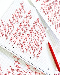 Calligraphy letters with red mini brush pen. Handwriting letters