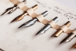 Calligraphy: Set of vingate fountain pens. Different metal nibs side by side laid on a paper diagonally. Black ink hand writing in the background. Artistic equipment.