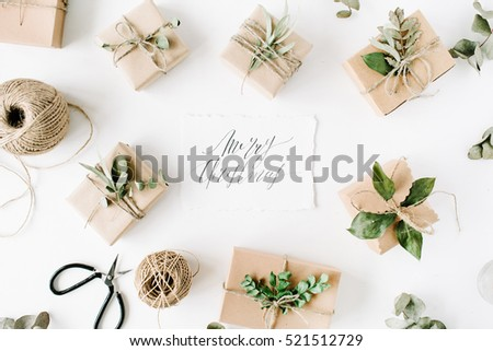 calligraphy words merry christmas and beauty arrangement frame of craft boxes and green branches on white background. flat lay, top view