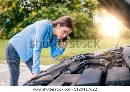 Calling Emergency Service. Car problems. Young woman using mobile phone while looking at broken down car on street. Woman caling autoservice because of car problem Stockfoto ©