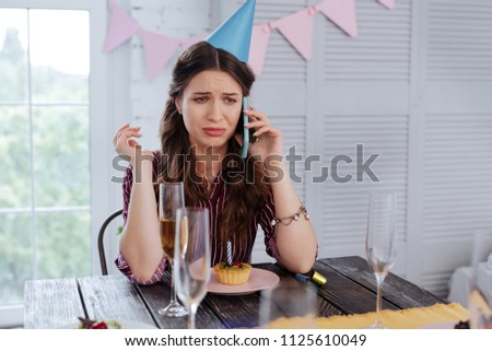 Calling guests. Emotional beautiful woman calling her guests on birthday while they running very late because of traffic #1125610049