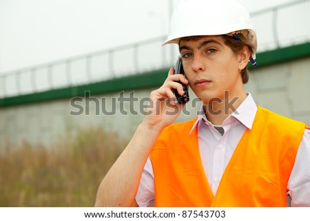 calling male architect with blueprint in construction site