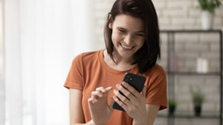 Calling to someone especial. Happy millennial woman stand at living room hold phone in hands dial number on touchscreen. Cheerful young lady surfing internet choosing name from contact list on cell