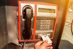Calling using the public payphone. Red payphone on a city street.