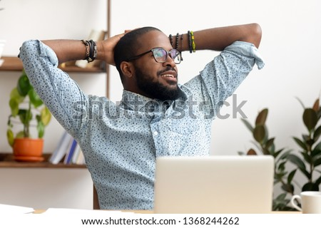 Calm african american business man take break at workplace relaxing finished work, happy black professional employee enjoy success rest from computer feeling stress relief peace of mind sit at desk