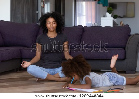 Calm african american mom doing yoga while quiet little mixed race kid daughter drawing on warm floor at home, black mother meditating for stress relief relaxing in living room with child daughter