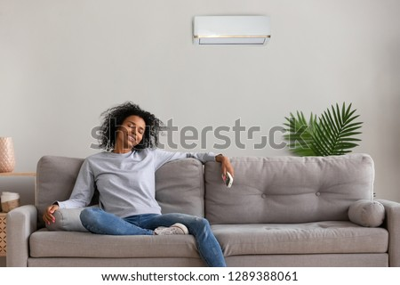 Calm African American woman sit on couch relaxing under air conditioner at home, peaceful black female hold remote controller resting on cozy sofa in apartment, happy girl enjoy fresh air