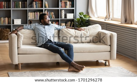 Calm African American young man sit relax on comfortable couch in living room look in distance thinking, relaxed biracial millennial male rest on sofa at home, breathe fresh air, stress free concept