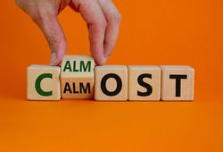 Calm almost. Male hand turns a wooden cube with words 'calm almost'. Beautiful orange background, copy space. Business and calm almost concept.