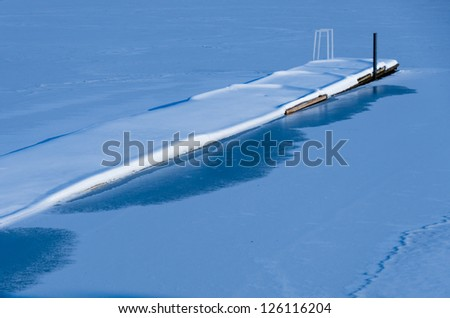 Calm and Deeply Snowed Jetty into Frozen Lake in Winter