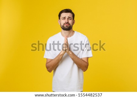 Calm and handsome. Portrait of handsome young man keeping hands clasped and looking thoughtful.