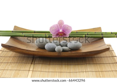 Calm and relaxing spa setting with orchid on towel with massage oil and stone