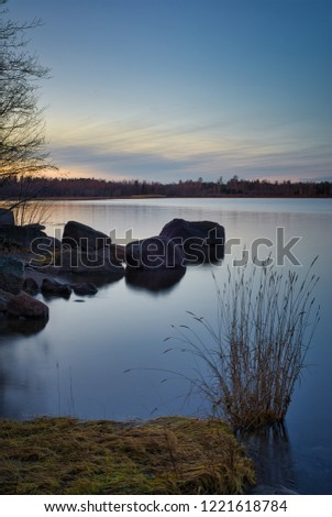 Calm and relaxing view of nature. Coast line with grass, rocks and sea in a beautiful mix in blue hour during sunset.
