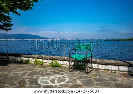 Calm and tranquil moment at lake Pamvotida near the Greek town Ioannina, spring morning green rope chair, selective focus, landscape view from Ioannina Island with the town in the background far away #1472775083