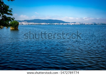 Calm and tranquil water of lake Pamvotida near the Greek town of Ioannina, early spring morning with fog, selective focus, landscape view from Ioannina Island with the town in the background far away #1472789774